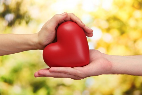 Red heart in woman and man hands, on green background to convey philanthropy of Barrister Executive Suites