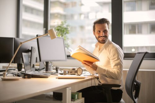 happy man holding a book in a private office space